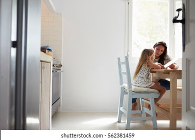 Mother And Daughter Sitting At Kitchen Table Reading Book