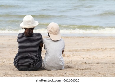 Mother and daughter sitting on the beach of summer