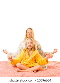 Mother and daughter sitting on a bed and doing yoga exercise
