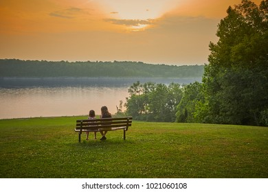 Mother and Daughter Sitting on a Bench next to a Lake at Sunset