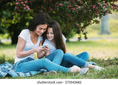 Mother and daughter sitting on the grass in the park