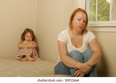 Mother and daughter sitting on a mattress looking sad