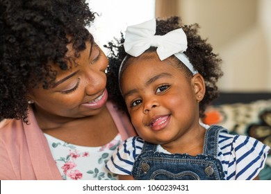 Mother and daughter sitting on a sofa smiling.