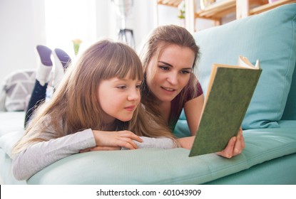 Mother and daughter sitting on sofa at home and reading book together