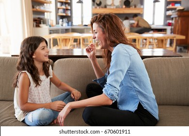 Mother And Daughter Sitting On Sofa Laughing Together