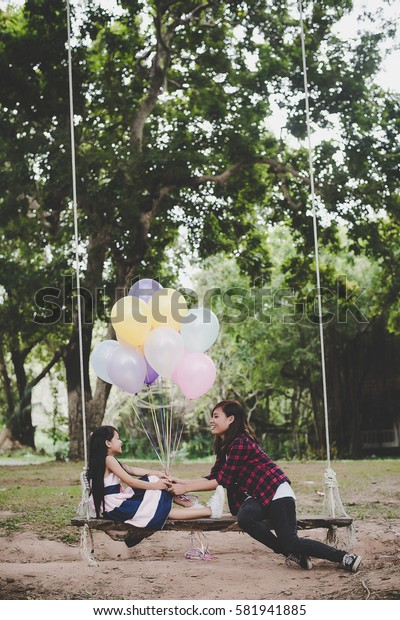 Mother with daughter sitting on swing with colorful of balloons relaxing outdoors together.