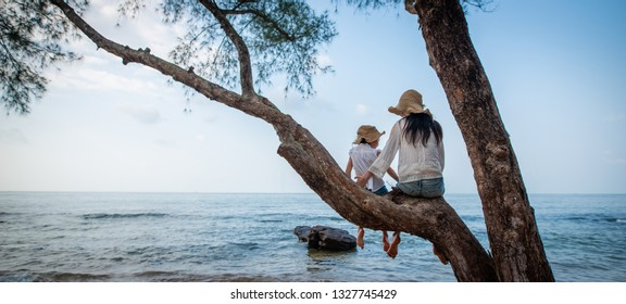 Mother and daughter sitting on a tree at the beach