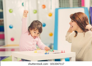 Mother and daughter sitting in a playroom, playing a ludo game; daughter happy because she won the game. Focus on the daughter