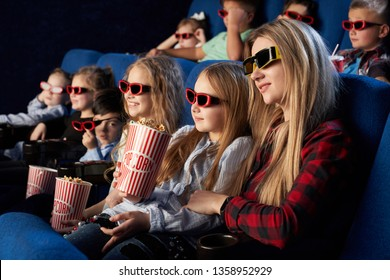 Mother and daughter sitting together in movie theatre, enjoying premiere of film. Children wearing in 3D glasses watching movie, holding popcorn buckets.