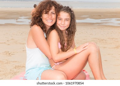 Mother and daughter sitting together on sand beach vacation