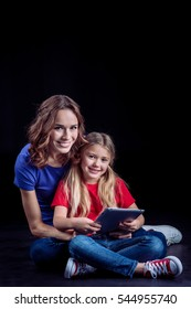 Mother and daughter sitting together and using digital tablet isolated on black