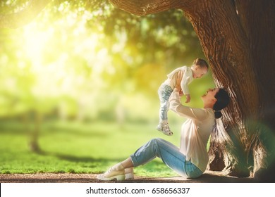 Mother and daughter sitting under the tree on summer lawn. Happy family playing outdoors. Pretty young mom having fun with her baby in the park outside.