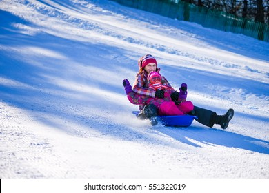 Mother and daughter with sledge on the piste daylight