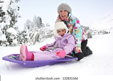 Mother and daughter sledging