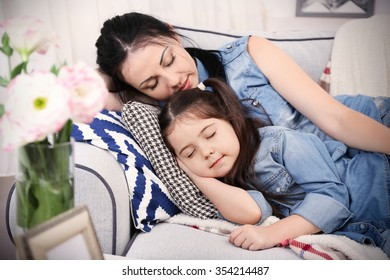 Mother and daughter sleeping on the sofa