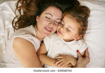 Mother and daughter sleeping together in bed. Mother and daughter embracing in bed asleep.