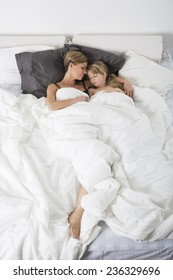 Mother and Daughter sleeping in a white bedroom from high angle view