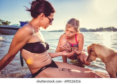 Mother, daughter and small yellow dog enjoying on the beach