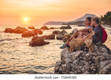 Mother and daughter with a small yellow dog hiking along the seashore during sunset