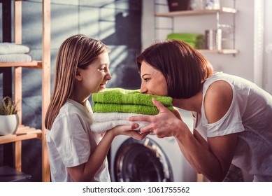 Mother and daughter smelling fresh green towels at laundry room