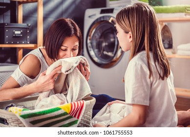 Mother and daughter smelling fresh towels at laundry room