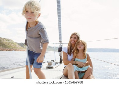 Mother, daughter and son enjoying trip on luxury private sailing yacht on summer vacation, outdoors smiling. Family day out activities, travel transportation leisure recreation exclusive lifestyle.