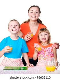 mother, daughter and son at the kitchen cooking an orange juice