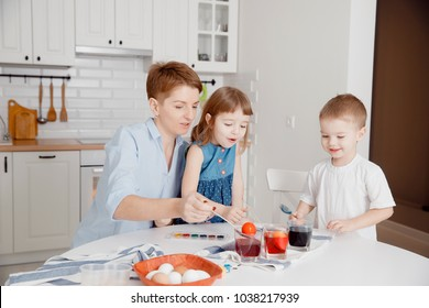 Mother, daughter and son paint eggs. White kitchen. A happy family is preparing for Easter.