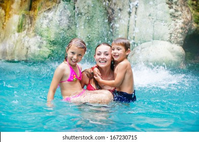 Mother and daughter and son at swimming pool smiling