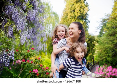 Mother with daughter and son walking in a summer park. They are all very fun. Mom carries her daughter on her shoulders. Seven surround flowering plants. Sunny summer day. Positive emotions.