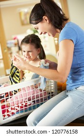 Mother And Daughter Sorting Laundry Sitting On Kitchen Counter