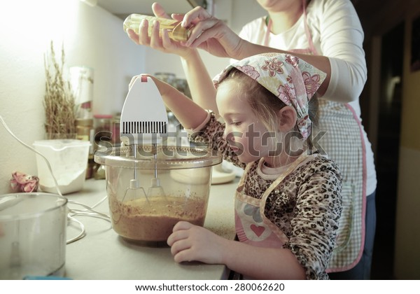Mother and daughter spending quality time together in the kitchen, preparing dough for homemade birthday cake. Family values, inclusion, learning through experience concept.