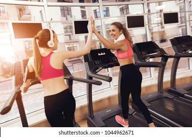 Mother and daughter in sportswear high five each other on treadmill at the gym. They look happy, fashionable and fit.