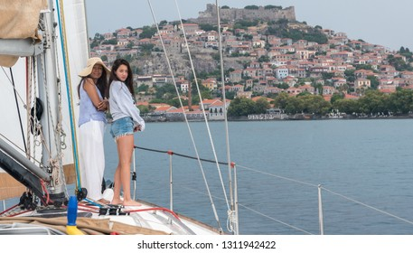 Mother and daughter stadning on the front of a sailbot with Molyvos lesvos in the background