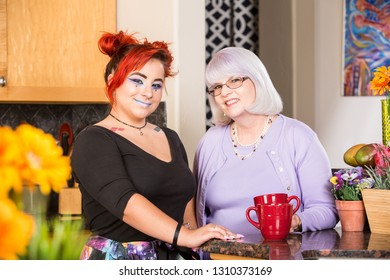 Mother and daughter stand in kitchen smiling