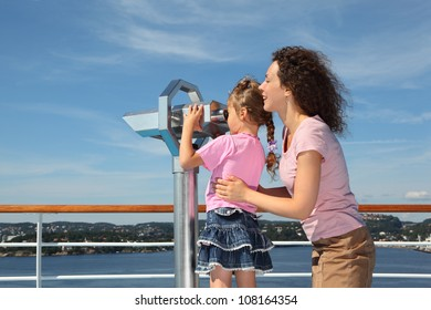 Mother and daughter stand on deck of ship; girl looks through binoculars at landscape