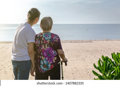 Mother and daughter stand together in front of the beach looking at the sea.  This shows the warmth love in family. This can be related with any article about family, elder, health.