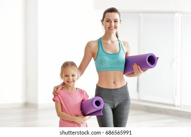 Mother and daughter standing with mats indoors