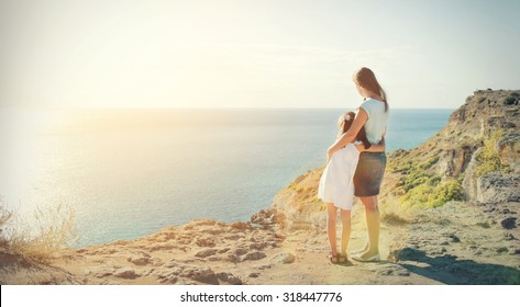 Mother and daughter standing on the edge of the mountain and look at the sea