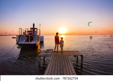 Mother and daughter standing on the pier  in the background of the sea, ship and sunset. Ukrainian landscape