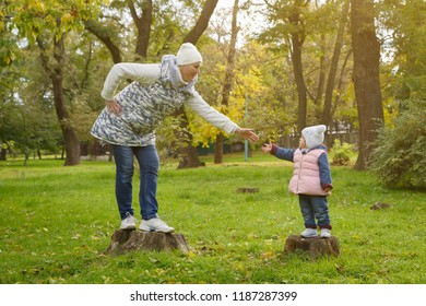 Mother and daughter are standing on the stumps in the parkland and are giving hands toward one another in a warm autumn day