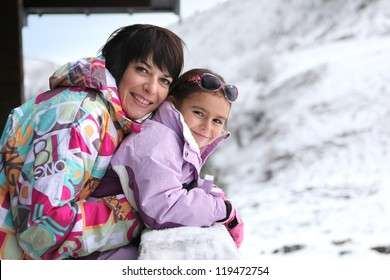 Mother and daughter stood by chalet