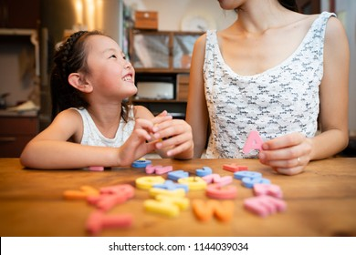 Mother and daughter studying the alphabet