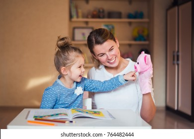 mother and daughter are studying with puppet pig