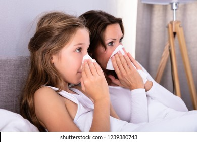 Mother And Daughter Suffering From Cold Blowing Her Nose With Handkerchief On Bed