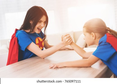 Mother and daughter in suits of superheroes. They compete in arm-wrestling.