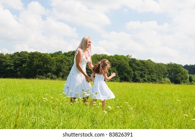 Mother and daughter in summer field