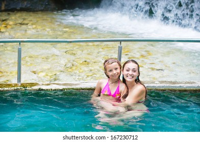 Mother and daughter at swimming pool smiling