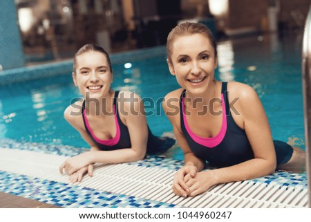 54e671a8e2 Mother and daughter in swimsuits at border of pool at the gym. They look  happy