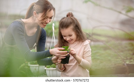 mother and daughter taking care of plants